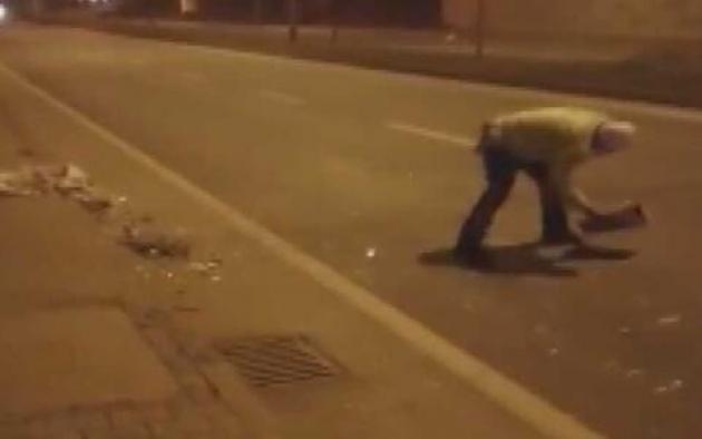 Elindeki kartonla yoldaki atıkları süpüren polise övgü